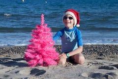 Διακοπές Χριστουγέννων Ένα χαριτωμένο παιδί που φορά ένα καπέλο Santa στην παραλία με ένα ρόδινο χριστουγεννιάτικο δέντρο στοκ εικόνες