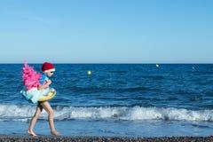 Διακοπές Χριστουγέννων Ένα χαριτωμένο παιδί που φορά ένα καπέλο Santa που περπατά στην παραλία με ένα ρόδινο χριστουγεννιάτικο δέ στοκ φωτογραφία με δικαίωμα ελεύθερης χρήσης