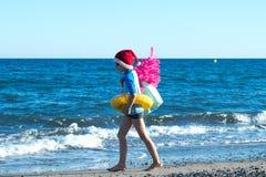 Διακοπές Χριστουγέννων Ένα χαριτωμένο παιδί που φορά ένα καπέλο Santa που περπατά στην παραλία με ένα ρόδινο χριστουγεννιάτικο δέ στοκ εικόνες