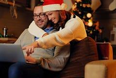 Διακοπές Χριστουγέννων Θηλυκό στο καπέλο Santa ` s που αγκαλιάζει ένα άτομο που χρησιμοποιεί ένα lap-top Στοκ φωτογραφία με δικαίωμα ελεύθερης χρήσης
