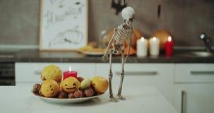 Διακοσμήσεις αποκριών στην κουζίνα, κεριά, κολοκύθες, πολύ ένας αστείος dacing ένας σκελετός στον πίνακα κουζινών απόθεμα βίντεο