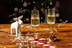 Διακοσμήσεις ελαφιών παιχνιδιών Χριστουγέννων στον πίνακα με τη σαμπάνια Στοκ φωτογραφίες με δικαίωμα ελεύθερης χρήσης