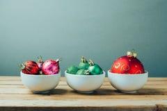 Διακοσμήσεις και διακοσμήσεις Χριστουγέννων στον ξύλινο πίνακα Τρία κύπελλα με τις σφαίρες Χριστουγέννων Αναδρομική επίδραση φίλτ Στοκ Εικόνες