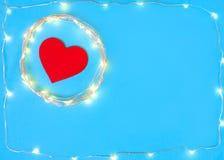 Διακοσμήσεις με μορφή της καρδιάς σε ένα μπλε υπόβαθρο με μια γιρλάντα Στοκ φωτογραφία με δικαίωμα ελεύθερης χρήσης