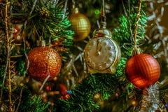 Διακοσμήσεις στο χριστουγεννιάτικο δέντρο - χρωματισμένες σφαίρες, ρολόι, γιρλάντες και φω'τα Στοκ εικόνες με δικαίωμα ελεύθερης χρήσης