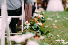 Διακοσμήσεις των άσπρων και πορτοκαλιών λουλουδιών με τις πράσινες διακοσμήσεις φύλλων υπαίθριος γάμος τελετή&sigma Στοκ Εικόνες