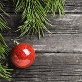Διακοσμήσεις των πράσινων κλάδων έλατου, κόκκινες σφαίρες Χριστουγέννων γυαλιού στοκ φωτογραφία