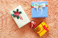 Διακοσμήσεις Χριστουγέννων και κιβώτιο δώρων στο υπόβαθρο ταπήτων Εύθυμο Chr Στοκ Εικόνες