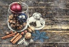 Διακοσμήσεις Χριστουγέννων, κανέλα, βάζο με τα καρύδια και τις διακοσμήσεις Χριστουγέννων, ξύλα καρυδιάς, φουντούκια εικόνα που τ Στοκ Εικόνες