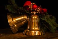 Διακοσμήσεις Χριστουγέννων - κουδούνια χεριών και ένας κλάδος fir-tree Στοκ Φωτογραφίες