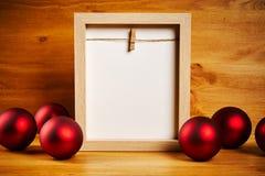 Διακοσμήσεις Χριστουγέννων σε έναν ξύλινο πίνακα με το κενό πλαίσιο Στοκ Φωτογραφία