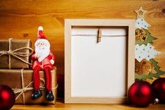 Διακοσμήσεις Χριστουγέννων σε έναν ξύλινο πίνακα με το κενό πλαίσιο Στοκ Φωτογραφίες