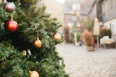 Διακοσμήσεις Χριστουγέννων σε ένα χριστουγεννιάτικο δέντρο υπό μορφή κόκκινων και χρυσών σφαιρών Χριστουγεννιάτικο δέντρο σε μια  Στοκ Εικόνες