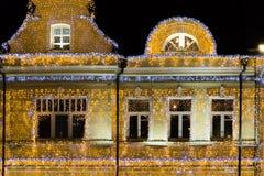 Διακοσμήσεις Χριστουγέννων σε μια πρόσοψη, ζωηρόχρωμα φω'τα διακοπών bokeh, φωτισμός νύχτας πόλεων magick Στοκ Φωτογραφίες