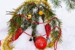 Διακοσμήσεις Χριστουγέννων στο δέντρο στο χειμερινό ξύλο Στοκ Εικόνες