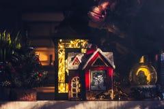 Διακοσμήσεις Χριστουγέννων στο ράφι, λίγη κόκκινη σφαίρα σπιτιών, φαναριών και χιονιού στοκ φωτογραφία