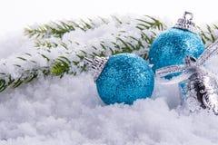 Διακοσμήσεις Χριστουγέννων - σφαίρες, κουδούνι και πράσινος κλάδος στο χιόνι Στοκ Εικόνες