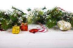 Διακοσμήσεις Χριστουγέννων, δώρα και κλάδοι έλατου σε έναν ξύλινο πίνακα Στοκ εικόνες με δικαίωμα ελεύθερης χρήσης
