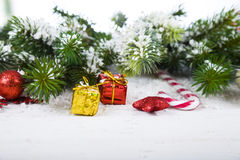 Διακοσμήσεις Χριστουγέννων, δώρα και κλάδοι έλατου σε έναν ξύλινο πίνακα Στοκ Φωτογραφίες