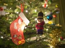 Διακοσμήσεις χριστουγεννιάτικων δέντρων με έναν στρατιώτη παιχνιδιών και μια γυναικεία κάλτσα στοκ φωτογραφία