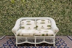 Διακοσμήστε τον καναπέ και τον τάπητα ενάντια στον πράσινο μικρό τοίχο δέντρων στοκ φωτογραφία με δικαίωμα ελεύθερης χρήσης