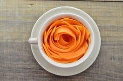 Διακοσμήστε το φλυτζάνι με τα καρότα φετών στον ξύλινο πίνακα στοκ εικόνα με δικαίωμα ελεύθερης χρήσης