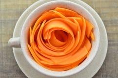 Διακοσμήστε το φλυτζάνι με τα καρότα φετών στον ξύλινο πίνακα στοκ φωτογραφία