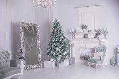 Διακοσμημένα κιβώτια χριστουγεννιάτικων δέντρων και δώρων στο καθιστικό μεγάλο άσπρο καθιστικό με εκλεκτής ποιότητας έπιπλα και έ στοκ εικόνες