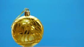 Διακοσμημένες κίτρινες σφαίρες Χριστουγέννων που περιστρέφουν στο μπλε υπόβαθρο απόθεμα βίντεο