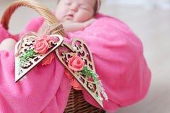 Διακοσμημένες ξύλινες καρδιές στο καλάθι, νεογέννητος ύπνος κοριτσάκι στο καλάθι, που βρίσκεται στο ρόδινο γενικό, χαριτωμένο παι Στοκ Εικόνες