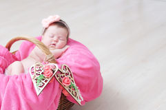 Διακοσμημένες ξύλινες καρδιές στο καλάθι στην εστίαση, νεογέννητος ύπνος κοριτσάκι στο καλάθι, που βρίσκεται στο ρόδινο γενικό, χ Στοκ Φωτογραφία