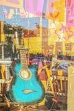 Διακοσμημένη η τυρκουάζ κιθάρα επάνω στην προθήκη με τις αντανακλάσεις και τις ρόδινες και κίτρινες ενώσεις boho πίσω στοκ εικόνα με δικαίωμα ελεύθερης χρήσης