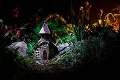 Διακοσμημένη φαντασία φωτογραφία Μικρό όμορφο σπίτι στη χλόη με το φως Παλαιό σπίτι στο δάσος τη νύχτα με το φεγγάρι Εκλεκτική εσ Στοκ Φωτογραφία
