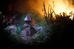 Διακοσμημένη φαντασία φωτογραφία Μικρό όμορφο σπίτι στη χλόη με το φως Παλαιό σπίτι στο δάσος τη νύχτα με το φεγγάρι Εκλεκτική εσ Στοκ φωτογραφίες με δικαίωμα ελεύθερης χρήσης