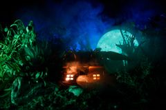 Διακοσμημένη φαντασία φωτογραφία Μικρό όμορφο σπίτι στη χλόη με το φως Παλαιό σπίτι στο δάσος τη νύχτα με το φεγγάρι Εκλεκτική εσ Στοκ φωτογραφία με δικαίωμα ελεύθερης χρήσης