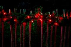 Διακοσμημένος με τα κόκκινα φώτα Χριστουγέννων στο φράκτη Στοκ εικόνες με δικαίωμα ελεύθερης χρήσης
