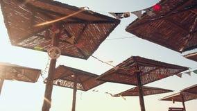 Διακοσμημένο άχυρο sunshades στη θυελλώδη παραλία θάλασσας πρωινού, ουρανός στο υπόβαθρο απόθεμα βίντεο