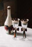 Διακοσμημένο γάμος μπουκάλι πολυτέλειας της σαμπάνιας και των γυαλιών στο βασιλικό ύφος στοκ εικόνα