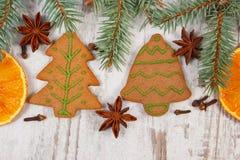 Διακοσμημένο μελόψωμο, κομψοί κλάδοι, καρυκεύματα στο παλαιό ξύλινο υπόβαθρο, διακόσμηση Χριστουγέννων Στοκ Εικόνα