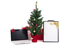 Διακοσμημένο χριστουγεννιάτικο δέντρο, κατάλογος υπολογιστών και δώρων σχετικά με το άσπρο backgr Στοκ Εικόνα