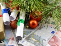 Διακοσμημένο χριστουγεννιάτικο δέντρο με τα χρήματα, δώρο, παραδοσιακές χειμερινές διακοπές Στοκ Φωτογραφία