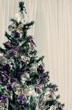 Διακοσμημένο χριστουγεννιάτικο δέντρο με τις πορφυρά και χρυσά κορδέλλες και τα μπαλόνια Στοκ Φωτογραφίες