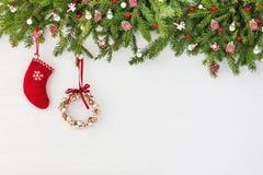 Διακοσμημένο χριστουγεννιάτικο δέντρο, στεφάνι Χριστουγέννων και κόκκινη κάλτσα στο άσπρο ξύλινο υπόβαθρο Διαστημική, τοπ άποψη α Στοκ Φωτογραφία