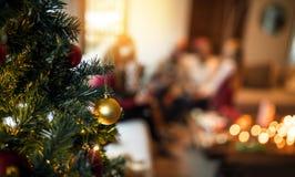 Διακοσμημένο χριστουγεννιάτικο δέντρο στο σπίτι με την οικογενειακή συνεδρίαση στο backgrou Στοκ Φωτογραφία