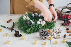 Διακοσμητής ανθοκόμων που κάνει το στεφάνι Χριστουγέννων Στοκ Φωτογραφία