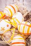 Διακοσμητικά αυγά Πάσχας, σε έναν αγροτικό ξύλινο πίνακα Στοκ εικόνες με δικαίωμα ελεύθερης χρήσης