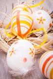 Διακοσμητικά αυγά Πάσχας, σε έναν αγροτικό ξύλινο πίνακα Στοκ Φωτογραφία