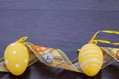 Διακοσμητικά αυγά Πάσχας, σε έναν αγροτικό ξύλινο πίνακα Στοκ Φωτογραφίες