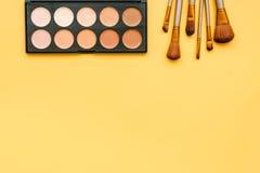 Διακοσμητικά καλλυντικά στην κίτρινη τοπ άποψη υποβάθρου Στοκ Εικόνες