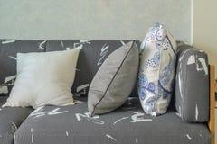 Διακοσμητικά μαξιλάρια που θέτουν στον γκρίζο καναπέ με την ξύλινη βάση στο livi Στοκ Φωτογραφίες